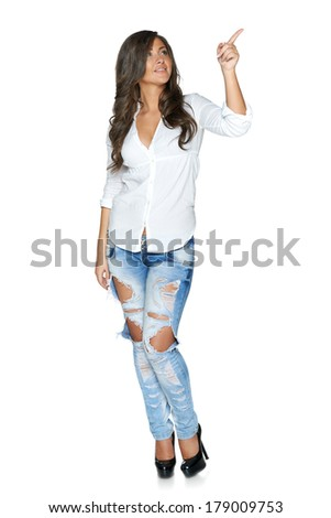 Full length young woman in funky ragged jeans and white shirt pointing to the side, isolated on white background - stock photo