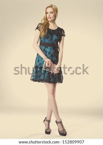 Full length young woman with curly blond hair holding purse posing - stock photo