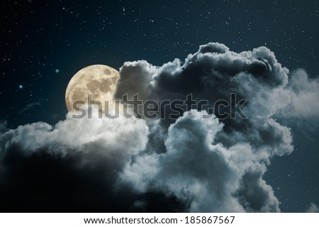 Full moon behind the clouds on a starry night - stock photo