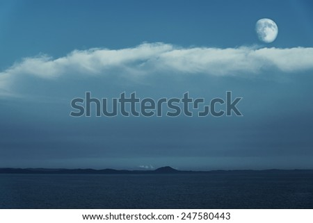 Full moon in blue cloudy sky over the sea - stock photo