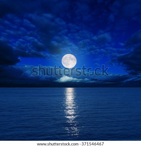 full moon in clouds over dark water with reflections on it - stock photo