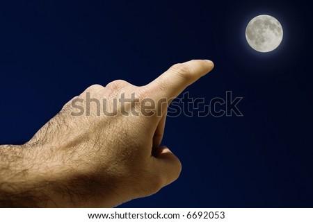 Full Moon. Man's Hand pointing the moon - stock photo