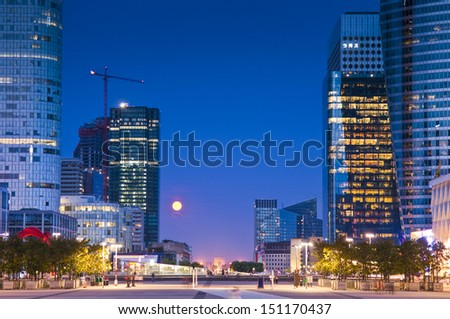 Full moon over the stunning La Defence Parisian business district bristling with skyscrapers that started life in the 1960's. Arc de triomphe visible on the horizon. - stock photo