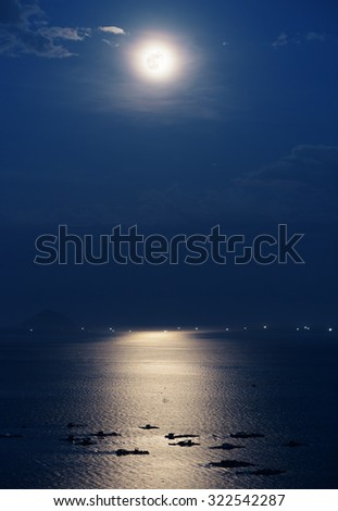 Full moon reflected in water of Nha Trang Bay of South China Sea in Vietnam at night. Marine farms illuminated by beautiful mysterious moonlight. Island and lights of ships are visible in background. - stock photo