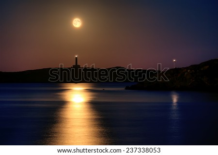 Full moon rise at the lighthouse of Ermoupolis in Syros island, Cyclades, Greece  - stock photo
