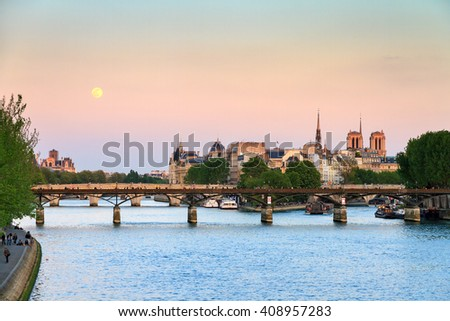 Full moon rise at twilight over the Seine with the Notre-Dame in the background in Paris, France - stock photo