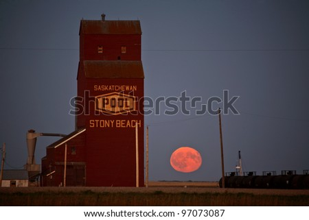 Full moon rising near Stoney Beach grain elevator - stock photo