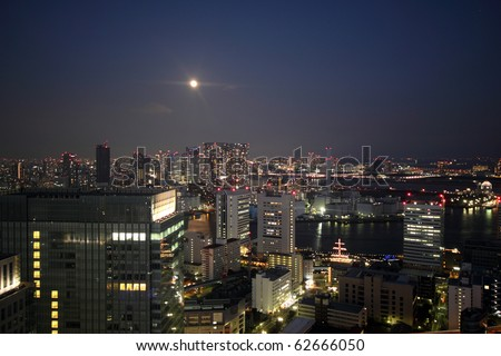 Full moon rising over night skyline of Tokyo, Japan with illuminated buildings and waterways - stock photo