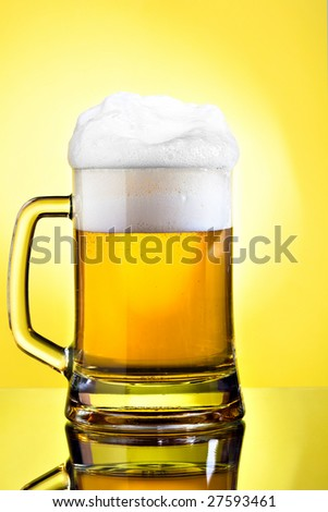 Full mug of lager beer on yellow - stock photo