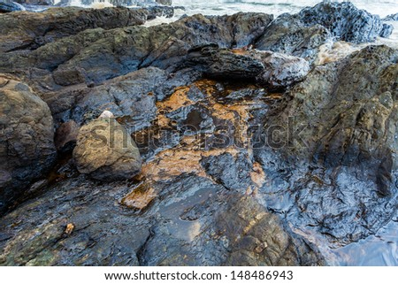 Full of crude oil on stone on oil spill accident on Ao Prao Beach at Samet island on July 31,2013 in Rayong,Thailand - stock photo