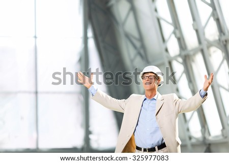 Full of energy. Pleasant emotional handsome architect rising his hands and smiling while evincing happiness - stock photo