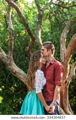 full of love stylish beautiful young caucasian couple on background of green park - stock photo