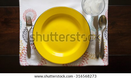 full place setting with yellow plate on patterned place mat  - stock photo