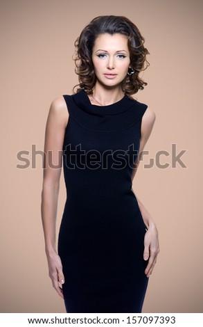Full portrait of a beautiful adult sensuality woman in black dress posing at studio - stock photo