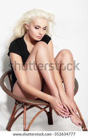 Full portrait of a blonde woman sitting on a chair. - stock photo