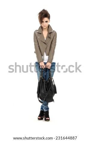 Full Portrait of young woman holding bag in jeans posing - stock photo