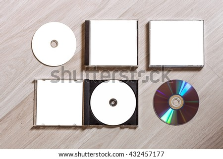 Full set compact disc template with plastic box case with white isolated blank for branding design and open box with booklet and back side. CD jewel case mock up with free space on wooden table. - stock photo
