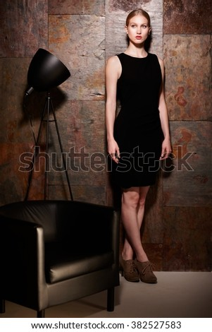 Full size studio shot of elegant blonde woman in little black dress standing over metal looking wall. - stock photo