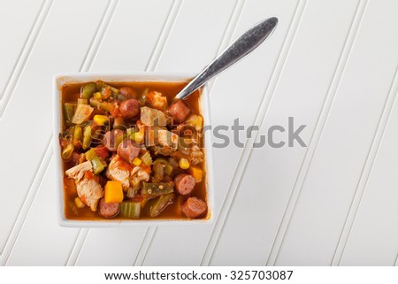 Full top view of a white square bowl of homemade chicken gumbo soup on white wooden wainscot  - stock photo