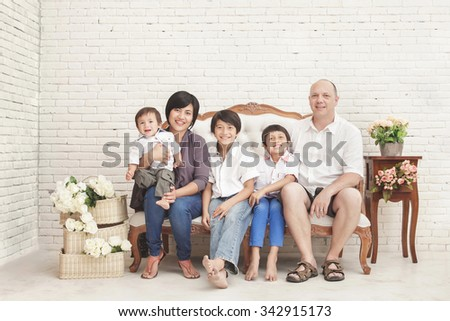 full view portrait of cheerful family at home sitting on sofa - stock photo