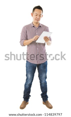 Fullbody Asian man using tablet computer standing over white background - stock photo