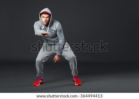 Fullbody portrait of young cool man dancing on dark gray background. - stock photo