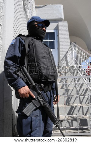 Fully armed and protected special forces soldier on the Mexican side of the US-Mexico border - stock photo
