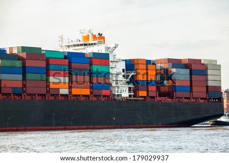 Fully laden container ship in port with its decks stacked with metal containers full of freight and cargo for international destinations - stock photo