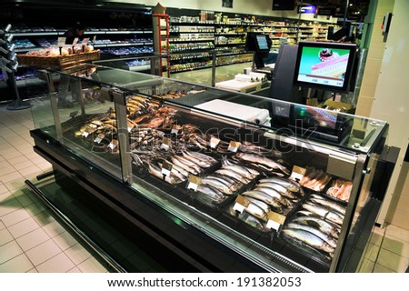 Fully loaded shelves with fish in a large supermarket - stock photo