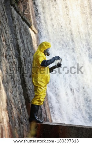 fully protected in coveralls ,boots,gloves and mask scientist examining sample of water - stock photo