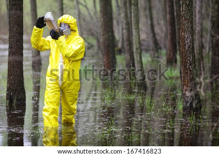 fully protected in uniform,boots,gloves and mask technician examining sample of water in plastic container in floods area - stock photo