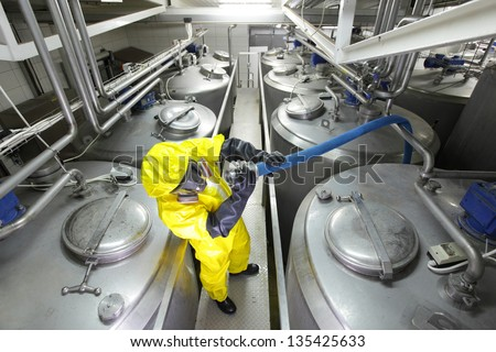 fully protected in yellow uniform,mask,and gloves technician  checking large process hose in factory - stock photo