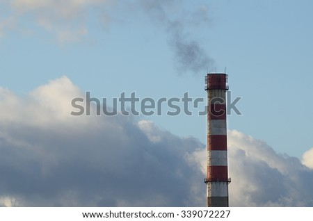 Fuming pipe against the cloudy sky. - stock photo