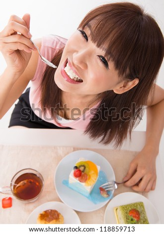 Fun Asian woman eating the cake inside house - stock photo