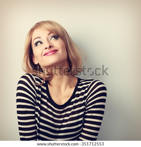 Fun beautiful thinking blond young woman in sweater looking up. Vintage toned portrait - stock photo