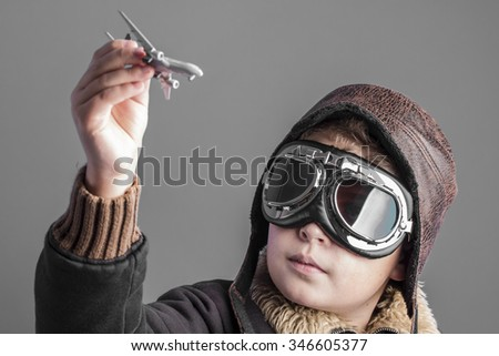 fun, child playing the aircraft pilot with hat and retro bomber jacket - stock photo