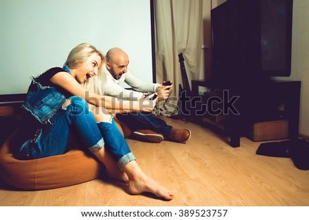 Fun couple enjoying computer games on tv. concept of leisure entertainment and fun - stock photo