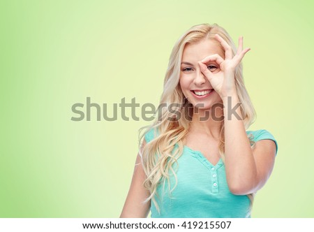 fun, emotions, expressions and people concept - smiling young woman or teenage girl making ok hand gesture over green natural background - stock photo