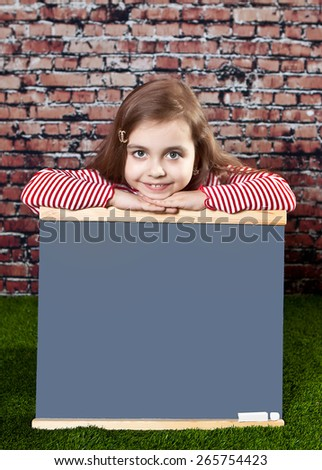 Fun girl sitting on the grass at an empty Board to draw against a brick wall - stock photo