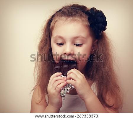 Fun happy kid girl eating dark chocolate. Closeup Vintage portrait - stock photo