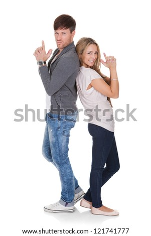 Fun image of a young attractive dueling couple standing back to back with their hands raised on a white background - stock photo