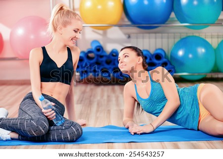 Fun in aerobics class. Two beautiful young women in sports clothing sitting on the yoga mat and chatting after exercising together  - stock photo