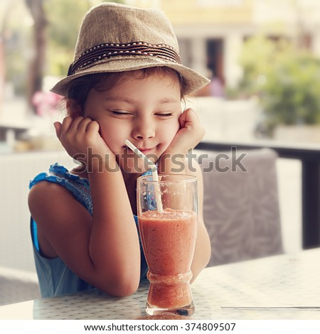Fun kid girl in hat screwing up her eyes and waiting the moment to drink the smoothie tasty juice on summer background in cafe. Toned closeup portrait - stock photo