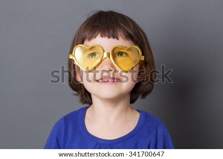 fun kid glasses concept - daydreaming preschool child wearing yellow heart-shape glasses for comic disco outfit or positive future,studio shot - stock photo