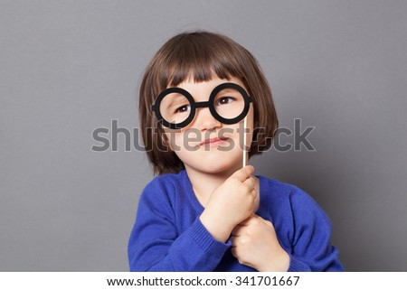 fun kid glasses concept - imaginative preschool child holding fake black round eyeglasses for playing like adult or dressing up as smart nerd,studio shot - stock photo