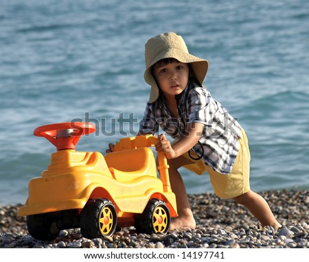 Fun little boy playing with car on the beach - stock photo