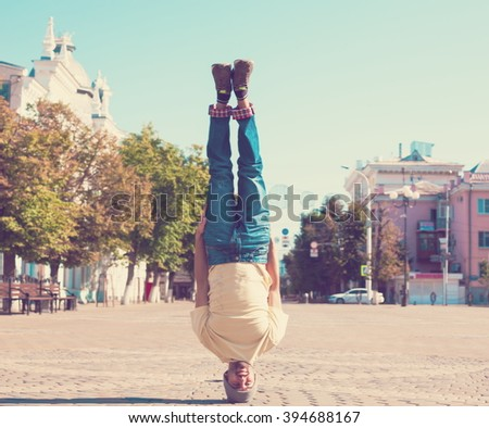 Fun man dancing. Has yellow t-shirt, blue jeans, slim sport body. Motion on great urban city. Amazing portrait. Sports acrobatic handstand. Fitness concept. Cool jump. Head over heels. - stock photo
