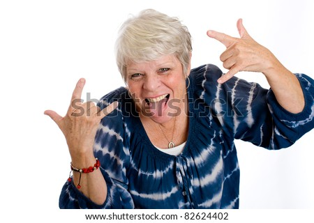 Fun, mature woman with her tongue sticking out and a big smile. - stock photo