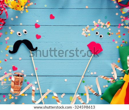 Fun photo booth accessories festive background with a loving couple formed from a mustache and set of luscious red female lips on rustic blue wooden boards with a frame of party streamers and bow tie - stock photo