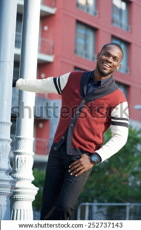 Fun portrait of a carefree young man smiling outdoors - stock photo